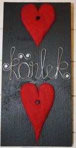 Svart tavla m två röda hjärtan å Kärlek