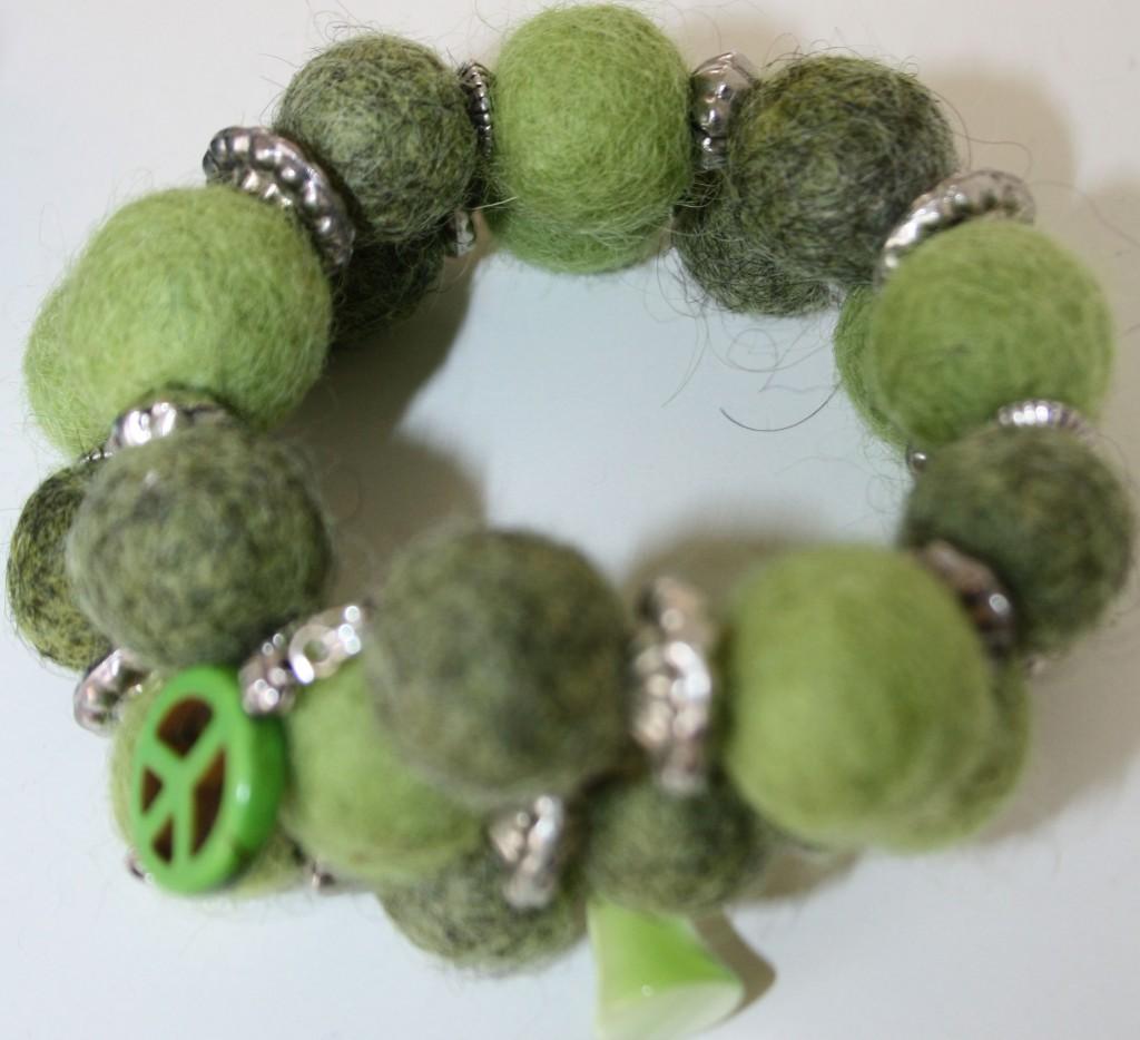 Armband med gröna tovade kulor, metalldelar och grön peacemärke